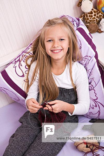 Mädchen sitzt auf einem Bett und strickt