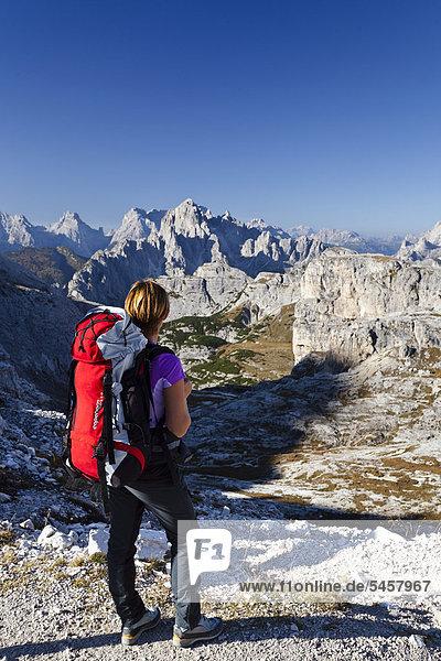 Wandererin auf dem Büllelejoch  beim Aufstieg zum Paternkofel oberhalb der Zsigmondy-Hütte  hinten die Cadinigruppe  Sexten  Hochpustertal  Dolomiten  Südtirol  Italien  Europa