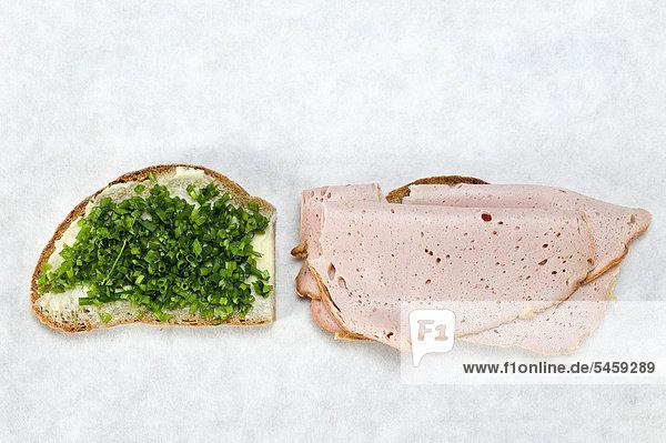 Scheibe Brot mit Schnittlauch und Scheibe Brot mit Leberkäse