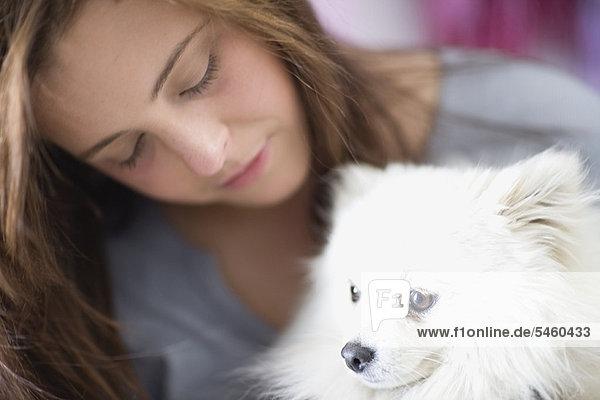 Teenage girl petting dog
