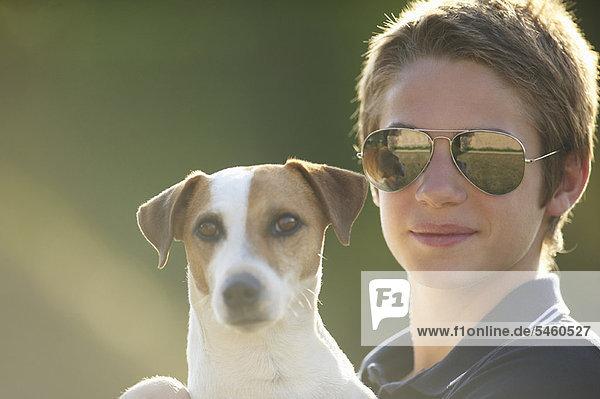 Teenage boy holding dog outdoors
