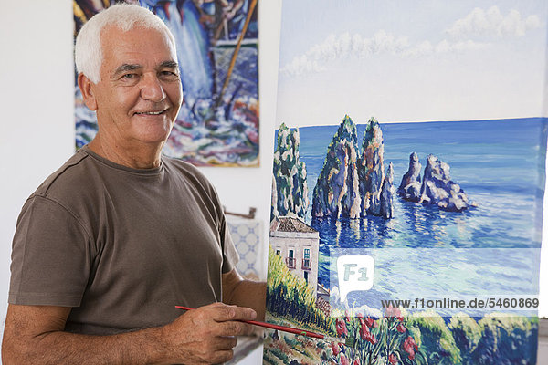 Older artist painting in studio