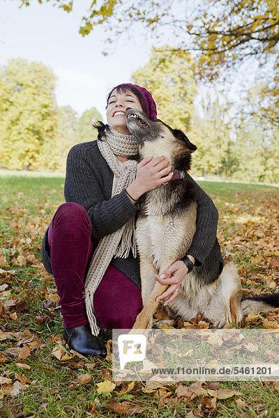 Lächelnde Frau streichelt Hund im Park