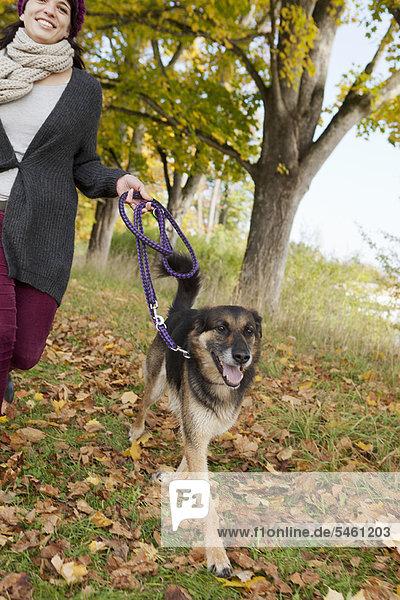 Lächelnde Frau spazieren gehender Hund im Park