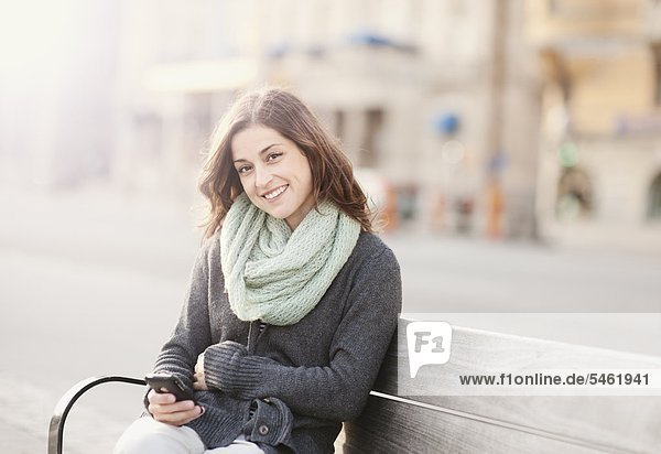 Portrait of young woman sitting on bench using phone