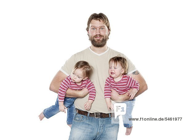 Studio portrait of father holding two baby daughters