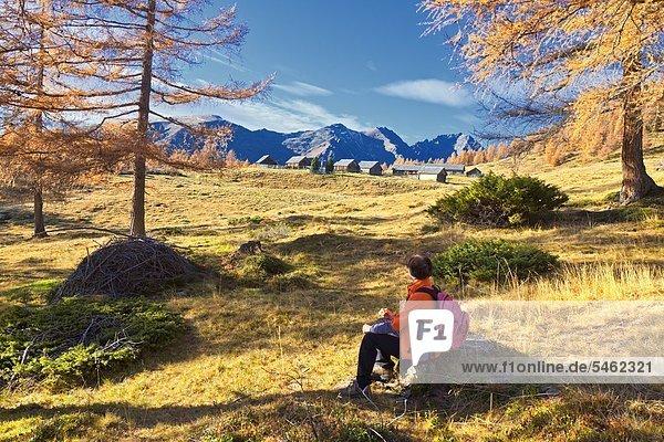 Frau sitzt auf einer Alm vor den Schladminger Tauern  Österreich