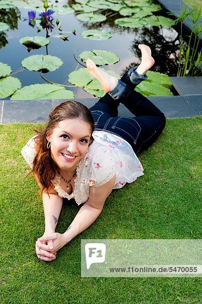 Portrait of a 24 year old brunette woman lying on her stomach on grass looking up at the camera