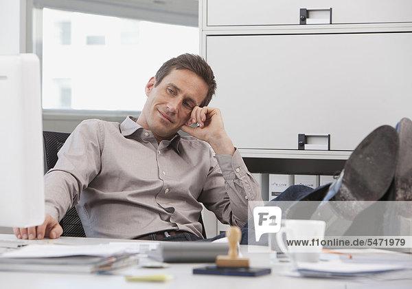 Mann sitzt entspannt an Schreibtisch  Füße auf dem Tisch