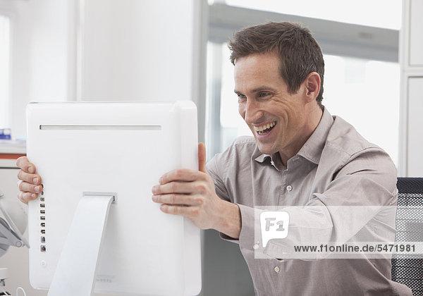 Mann packt erfreut seinen Bildschirm
