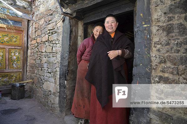 Zwei tibetische Nonnen stehen vor der Klosterküche des Nonnenklosters in den Bergen von Kloster Reting  Mount Gangi Rarwa  Himalaya  Lhundrup County  Zentraltibet  Tibet  China