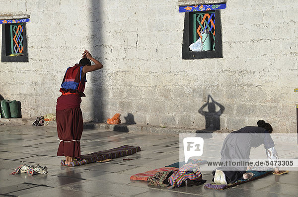 Tibetan Buddhism  Tibetan pilgrims and monks prostrating in front of Jokhang Temple  Barkhor  Lhasa  Tibet  China  Asia