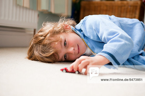 Young boy lying on his side playing with a toy car