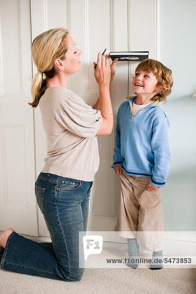 Mutter misst ihren Sohn an einer Tür mit einem Buch.