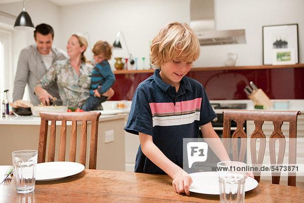 Sohn hilft beim Tischdecken mit Eltern und Bruder  die in der Küche sichtbar sind