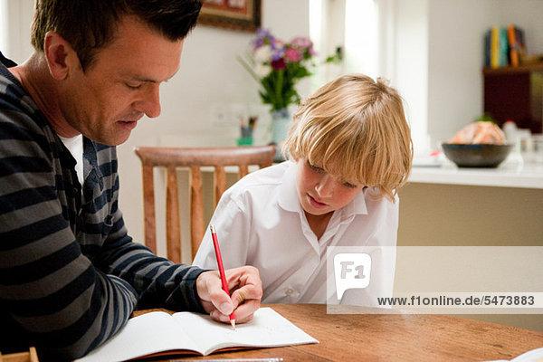 Vater hilft dem Sohn bei seinen Hausaufgaben
