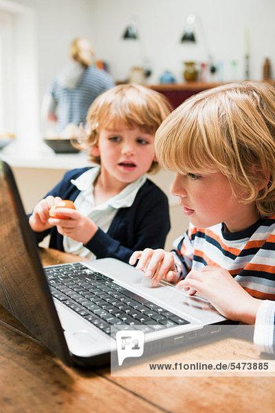 Kleiner Junge mit Laptop und seinem jüngeren Bruder mit Blick auf den Monitor