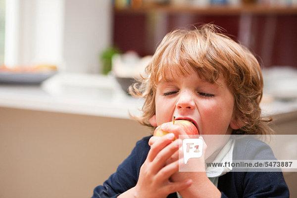 Kleiner Junge  der einen Apfel isst