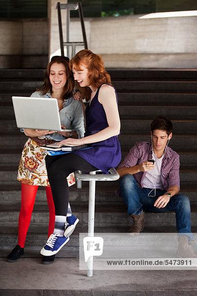 Zwei young Woman looking at Laptop unten Schritte