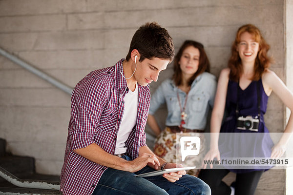 Young man using a digital tablet with young women in the background