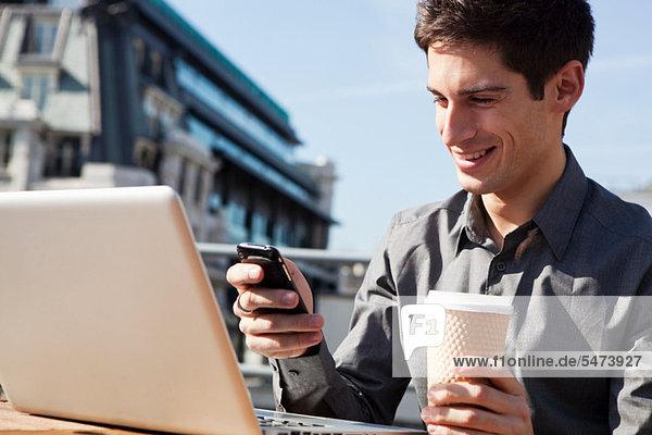 Junger Mann arbeiten im Freien mit seinen Laptop und Handy
