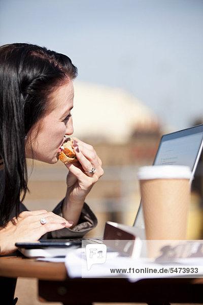 Junge Frau isst Sandwich mit Laptop