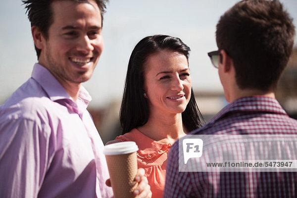 Drei Freunde mit einem Chat über einen Kaffee