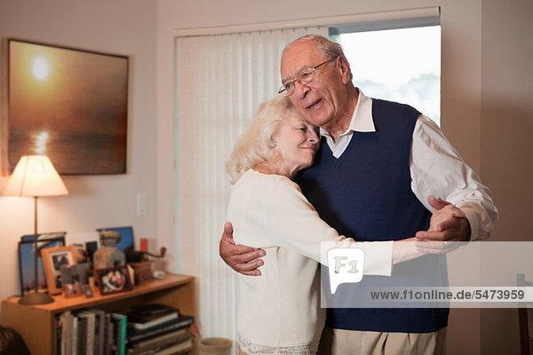 Seniorenpaar tanzt im Wohnzimmer