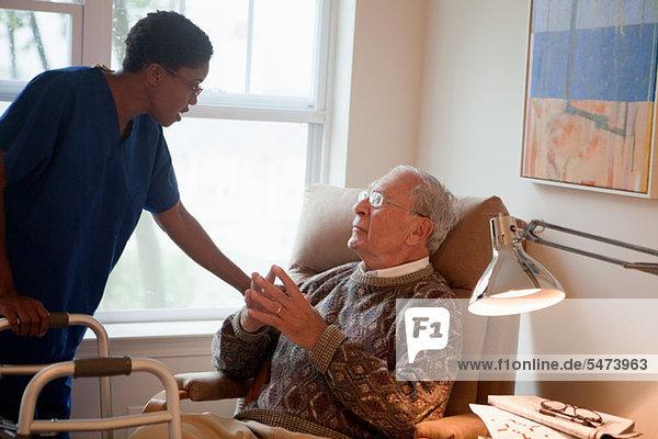 Krankenschwester  die sich um den älteren Mann zu Hause kümmert.