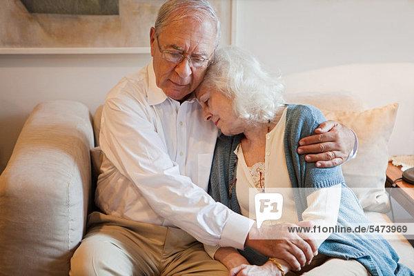Seniorenpaar umarmt sich zu Hause auf dem Sofa