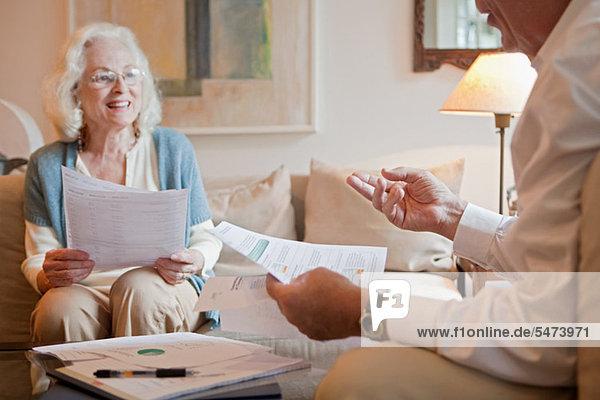 Seniorenpaar diskutiert zu Hause über den Papierkram