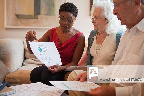 Mittlere erwachsene Frau  die dem älteren Paar finanzielle Papiere zeigt.