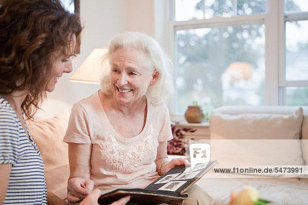 Seniorin und Tochter beim Durchblättern des Fotoalbums