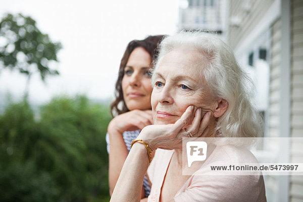 Senior Woman and Daughter relaxing auf Veranda