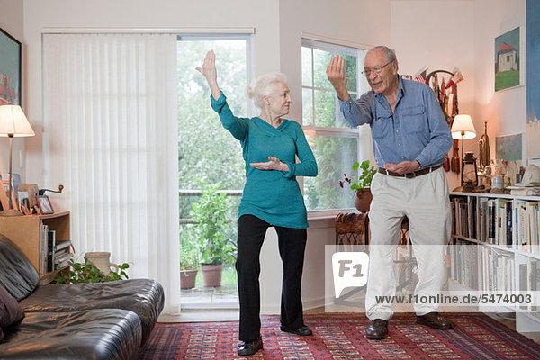Seniorenpaar beim Tai Chi im Wohnzimmer