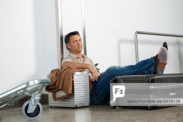 Mann schläft auf Gepäck im Flughafen