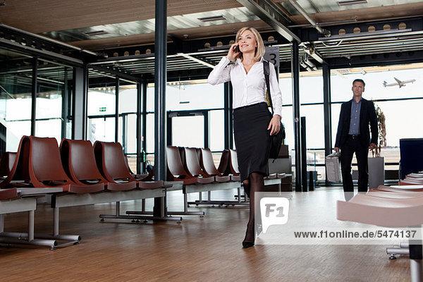 Geschäftsfrau mit Telefon am Flughafen
