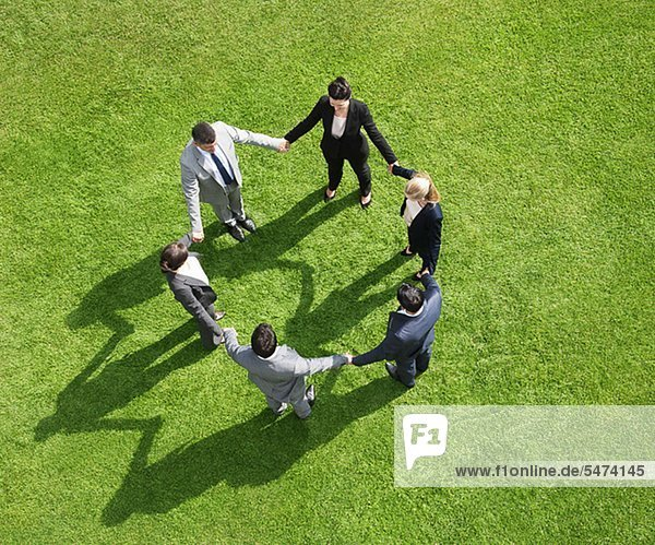 Geschäftsleute halten sich im Freien in einem Kreis an den Händen