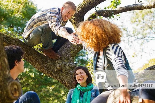Mittlerer Erwachsener Mann im Baum  der nach Freunden greift.