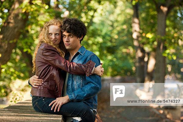 Junges Paar umarmen an Wand im park