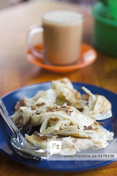 Typische malaysischen Frühstück  Roti Canai und Tasse Teh tarik
