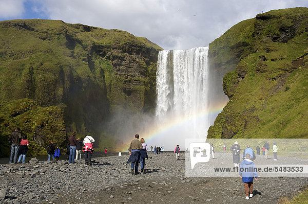 Tourists at the SkÛgafoss waterfall with rainbow  south coast  Iceland  Europe