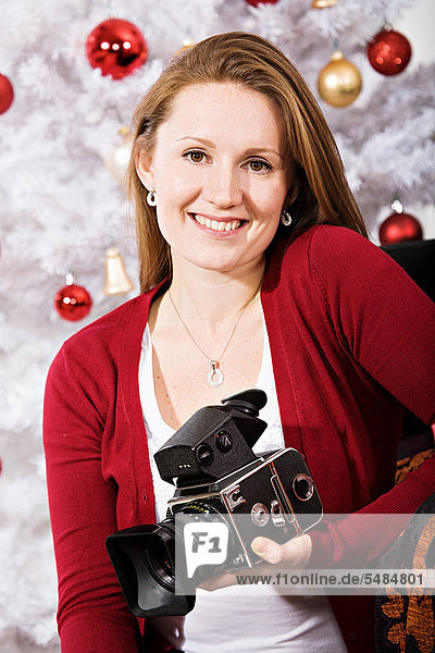 Junge Frau mit einer Kamera vor einem Weihnachtsbaum