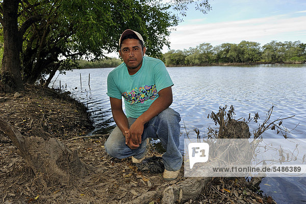 Young man on the shore of a pond where he is operating a crab farm  Las Mesitas  Jiquilisco  El Salvador  Central America  Latin America