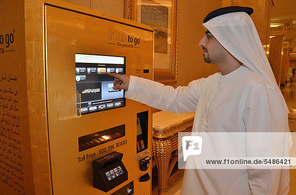 'Local man wearing a dishdasha  traditional white robe  in front of the gold machine ''Gold to go'' in the Emirates Palace Hotel  Abu Dhabi  United Arab Emirates  Arabia  Asia'