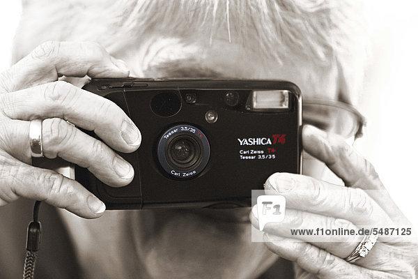 Frau fotografiert mit analoger Kamera