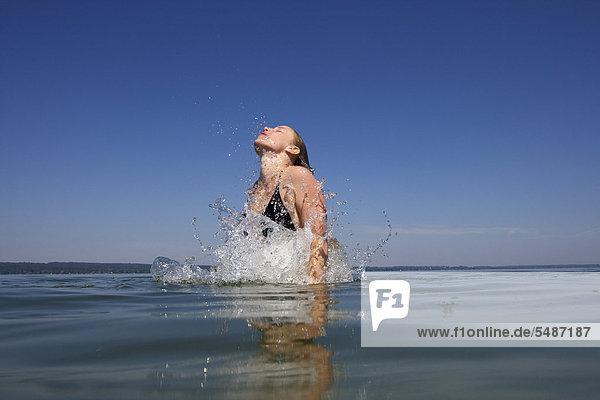 Junge Frau taucht aus Wasser auf