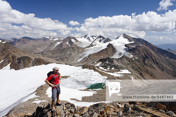 Hiker ascending Finailspitz Mountain in Schnalstal Valley via Tisental Valley  looking towards Similaun and Hintere Schwaerze mountains  below is Tisenjoch Pass and Hauslabjoch Pass  the site where Oetzi the Iceman was discovered  Alto Adige  Italy  Europe