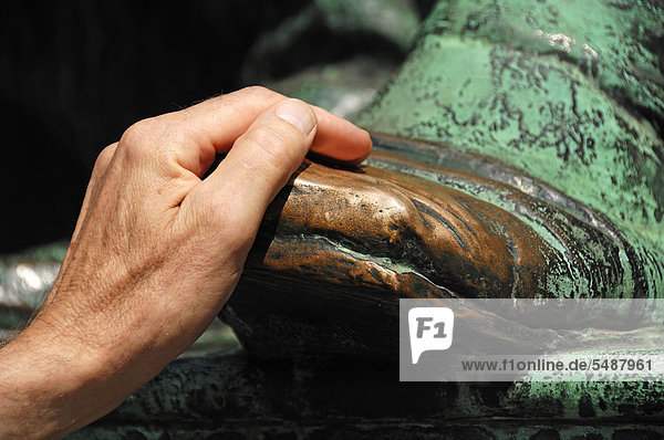 Hand on the bare  bronze shoe of the statue of Johann Wolfgang von Goethe  brings good luck  on the corner of Opernring street and Goethestrasse street  Vienna  Austria  Europe