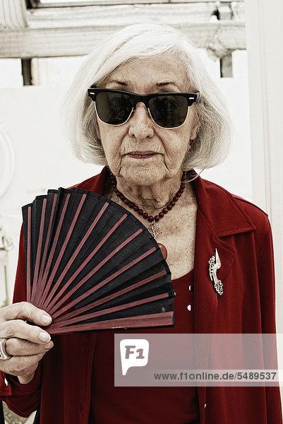 Senior woman with folding fan  portrait